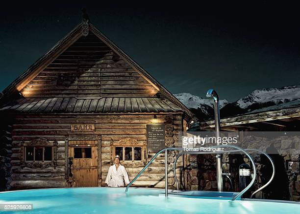 Holidaymaker standing outside wooden thermal bath, by swimming pool