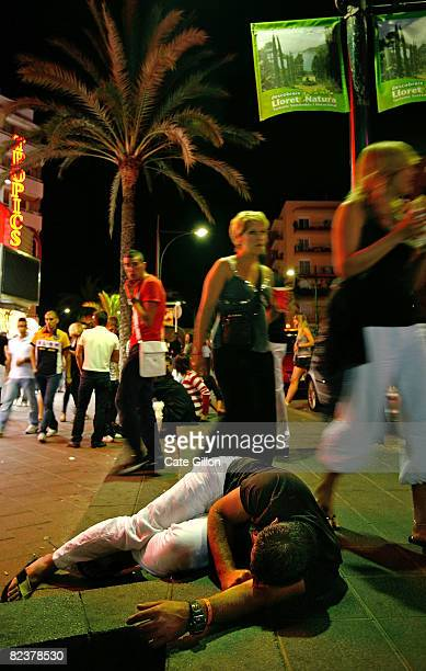 A holidaymaker who has had too much to drink sleeps on the pavement on 'The Strip' during a night out on August 16 2008 in Lloret de Mar Spain...