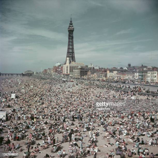 Holidaymakers and visitors enjoy a day on the beach at the seaside resort of Blackpool in Lancashire in August 1953 In the background stands the...