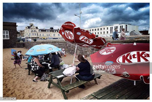 Holidaymakers brave the weather and shelter under an umbrella as another turns inside out in the wind on the beach on July 29 2010 in WestonsuperMare...