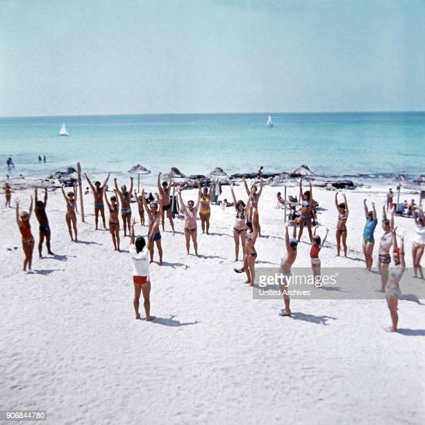 Holidaymakers doing some animations at the beach Spain late 1970s
