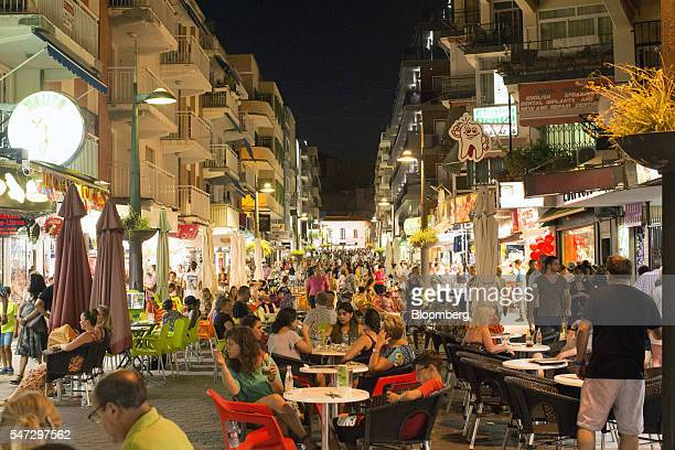 Holidaymakers eat and drink at the outdoor terraces of bars and restaurants at night in Benidorm Spain on Tuesday July 12 2016 Spain registered...