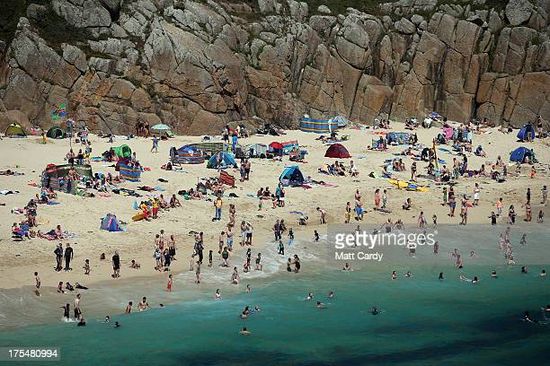 Holidaymakers enjoy the beach at Porthcurno below the Minack Theatre on August 2 2013 in Porthcurno near Penzance Cornwall The play is one of a...