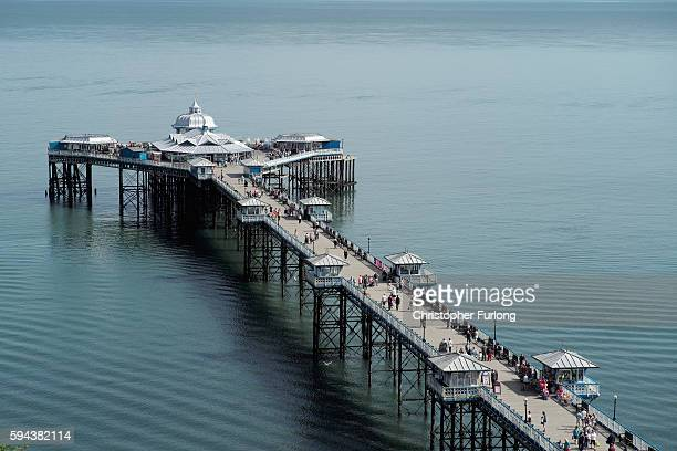 Holidaymakers enjoy the fine weather as they stroll on the pier at Llandudno on August 23 2016 in Llandudno Wales As many Britons head to the seaside...
