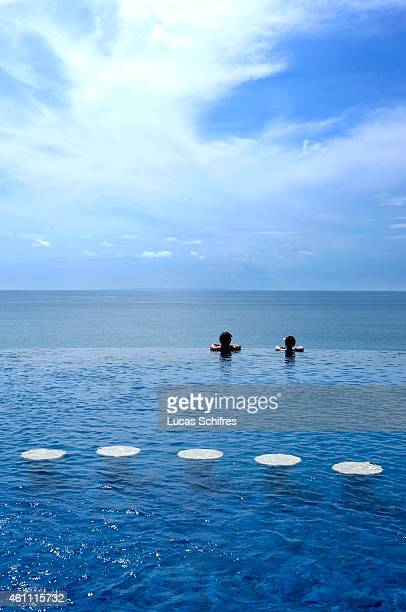 Holidaymakers enjoy the swimming pool overlooking the sea at Blue Point resort on February 19 2010 in Uluwatu Southern Bali Indonesia