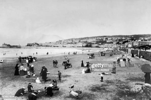 Holidaymakers enjoy theselves on the sands in the coastal resort of WestonsuperMare in North Somerset circa 1880