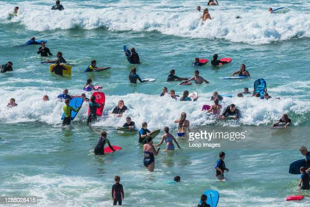 Holidaymakers enjoying themselves in the sea at Fistral in Newquay in Cornwall.