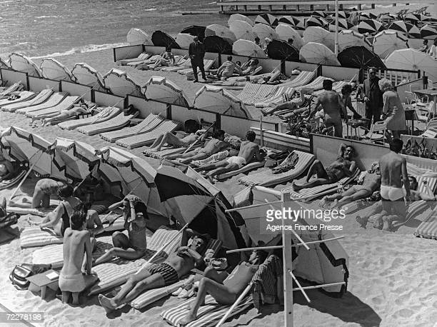 Holidaymakers in Cannes shelter from the Mistral behind umbrellas 4th May 1967