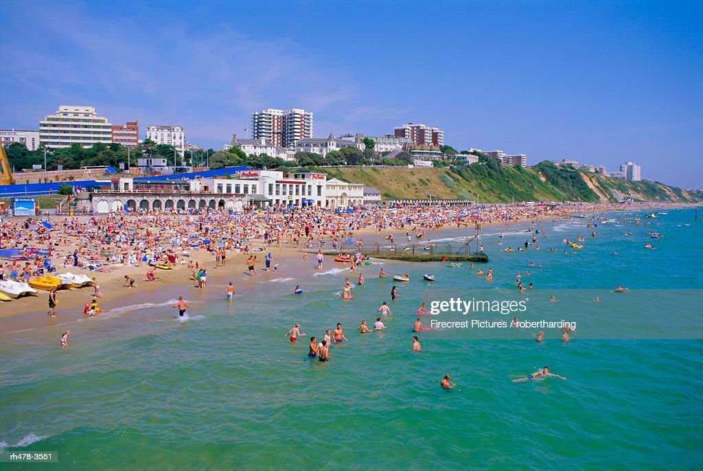 Holidaymakers in the sea and on the beach, Bournemouth, Dorset, England, UK : Stockfoto