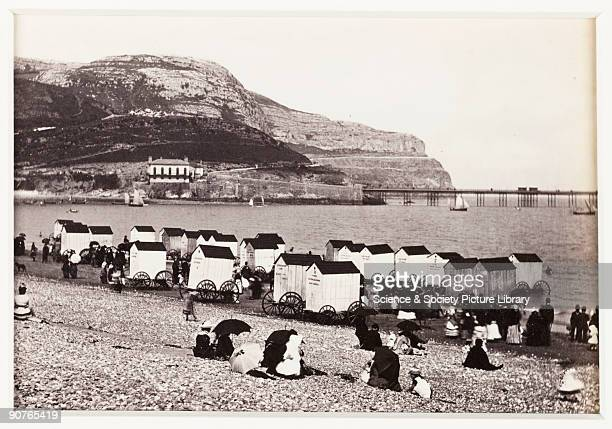 Holidaymakers many with umbrellas on the beach at Llandudno on the north coast of Wales Bathing machines some labelled �Ladies� are in use as a few...