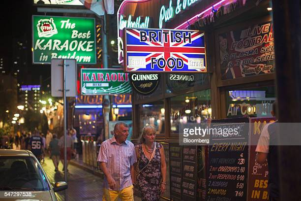 Holidaymakers pass bars advertising karaoke and British food in Benidorm Spain on Tuesday July 12 2016 Spain registered record tourism year in 2015...
