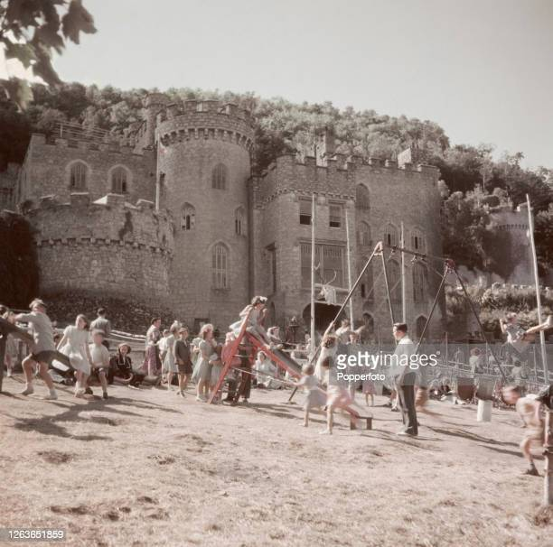 Holidaymakers play on swings and slides at a playground in the grounds of Gwrych Castle country house near the town of Abergele in north Wales in 1952