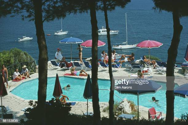 Holidaymakers relax beside the swimming pool of Il Pellicano Hotel in Porto Ercole Tuscany August 1980