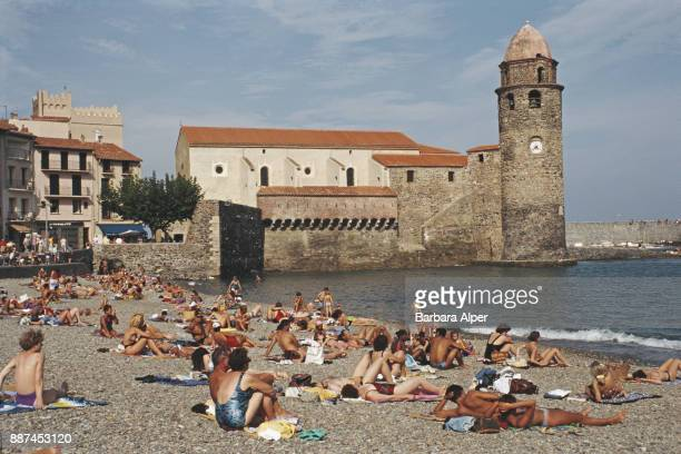 Holidaymakers relaxes across the bay in Collioure in the background is NotreDamedesAnges Church France August 1993