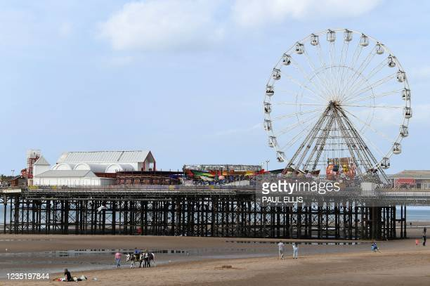 Holiday-makers ride donkeys on the beach in Blackpool, north west England on September 4, 2021. - Blackpool's Illuminations lights festival crowns an...