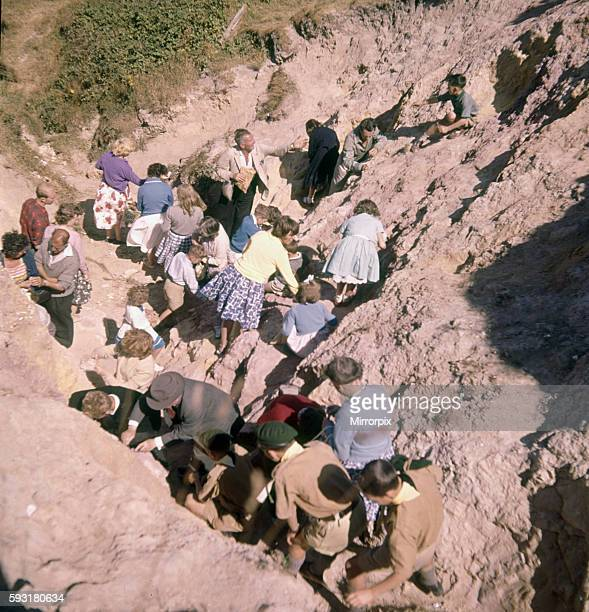 Holidaymakers scratching out the coloured sands from the cliff face at Alum Bay, Isle of Wight. August 1961.