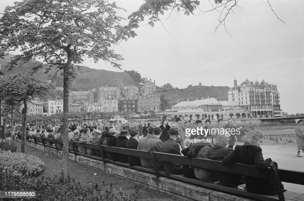 Holidaymakers seated on benches watch visitors walking along the promenade as they enjoy a wartime vacation at the seaside resort town of Llandudno...