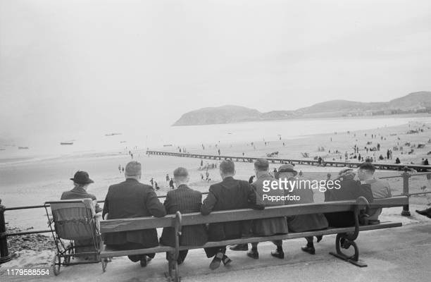 Holidaymakers sit on a bench to watch visitors playing on the beach as they enjoy a wartime vacation at the seaside resort town of Llandudno Wales...