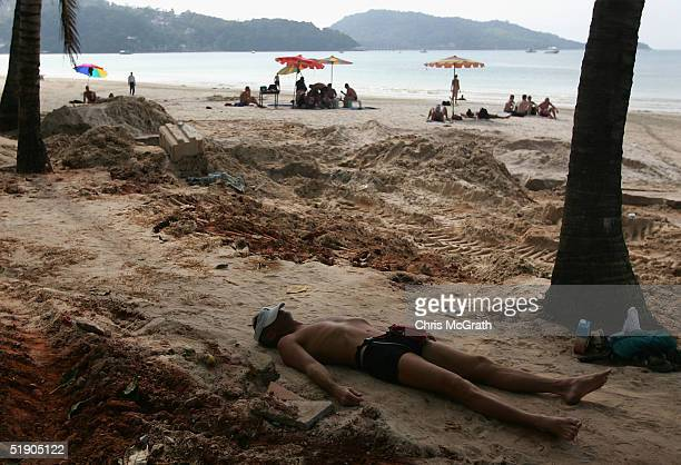 Holidaymakers sunbathe amongst the devastated shoreline of Patong Beach December 31 2004 in Patong Thailand Tourists have begun to return to the...