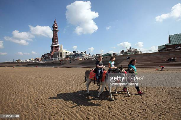 Holidaymakers take a donkey ride on the beach next to the refurbished Blackpool Tower on September 1 2011 in Blackpool England After a 20million GBP...