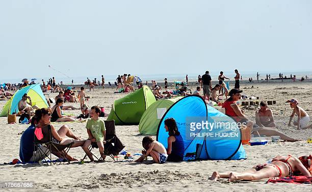Holidaymakers take a sun bath on August 5 2013 on a beach in BercksurMer northern France AFP PHOTO PHILIPPE HUGUEN