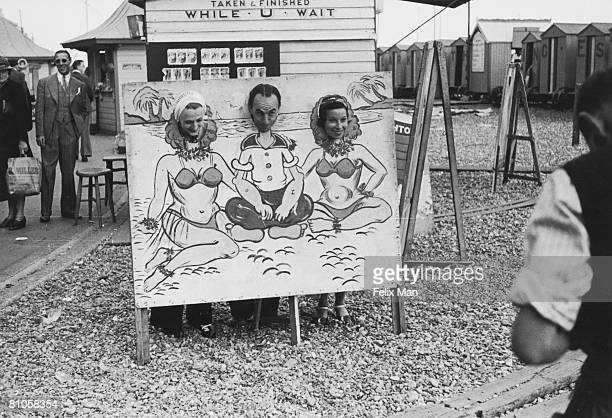 Holidaymakers using a cutout to pose as Popeye and a pair of exotic ladies for a beach photographer Brighton 12th August 1939 Original publication...
