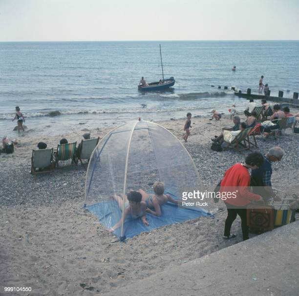 Holidaymakers using plastic transparent tents rented out from the Urban Council of Littlehampton for ten shillings a day UK June 1968