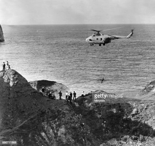 Holidaymakers watch as a RAF winchman helps the injured party aboard a Westland Whirlwind HAR10 helicopter as it hovers over the cliffs at...