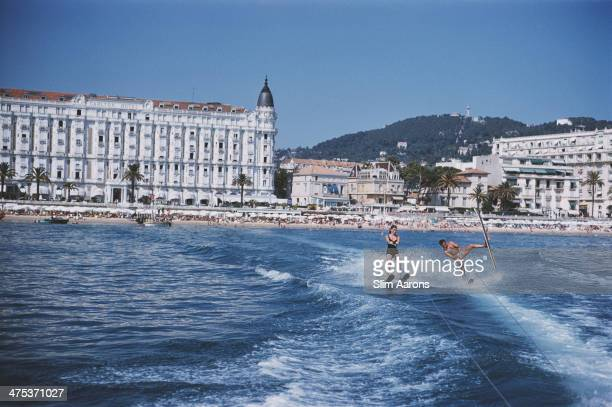 Holidaymakers waterskiing in front of the Carlton Hotel Cannes 1958