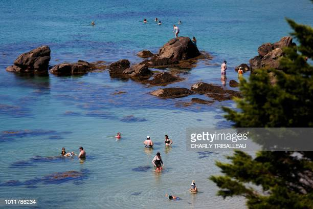 Holidaymarkers enjoy the beach and the sea on the Island of Chausey off the coastal town of Granville northwestern France on August 5 2018