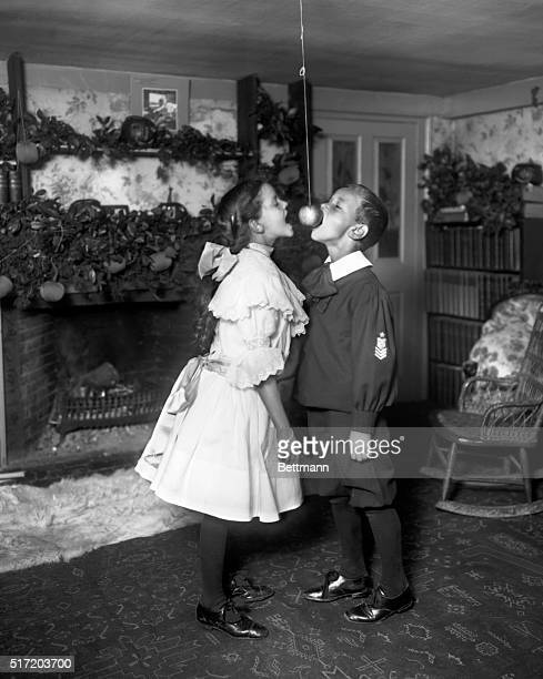 US Holidays and how the childen celebrated them Halloween Apple biting Boy and girl in tough contest Photograph circa 1900
