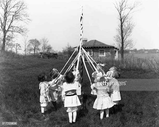 US Holidays and how the childen celebrated them May Day Children around May Pole the braiding at midway Photograph circa 1900