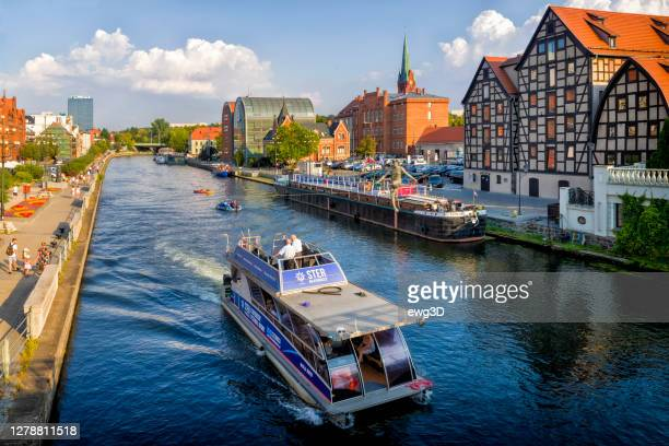 holidays in poland - brda river with old barge and old town buildings in bydgoszcz - bydgoszcz stock pictures, royalty-free photos & images
