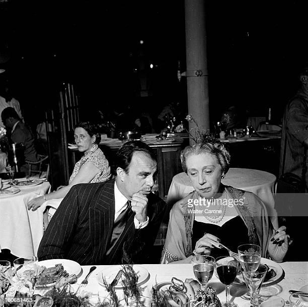 Holidays On The French Rivieira juillet 1951 Portrait d'Ali KHAN discutant à table avec une personne non identifiée en vacances sur la Côte d'Azur