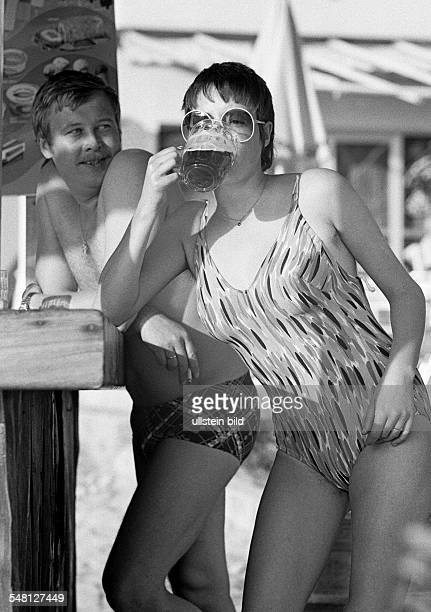 Holidays, tourism, young couple in bathing wear standing at a bar, girl drinks a beer, aged 25 to 30 years, Spain, Balearic Islands, Majorca,...