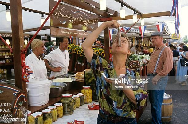 Holland, Amsterdam, Albert Cuyp street market, woman eating herring