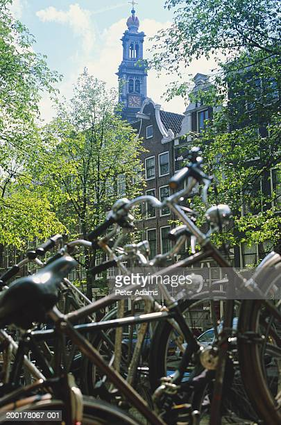 holland, amsterdam, bicycles on rack, church in background - travel14 stock pictures, royalty-free photos & images