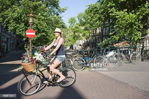 Holland, Amsterdam, Woman cycling on bike decorated with flowers