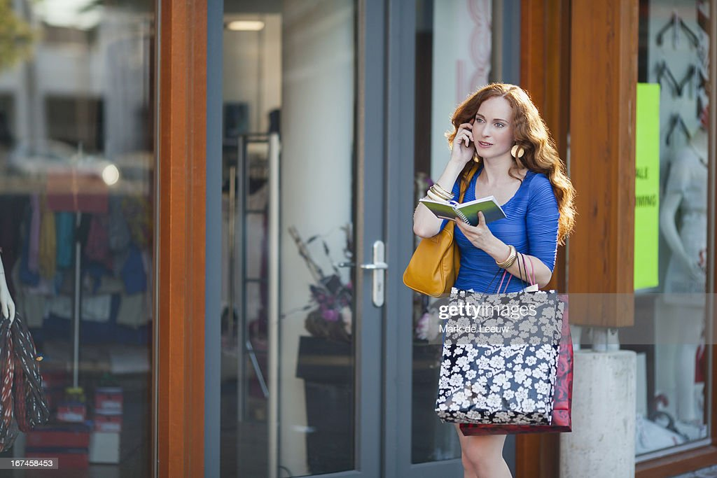 Holland, Goirle, elegant woman walking street and talking on mobile phone : Stock Photo