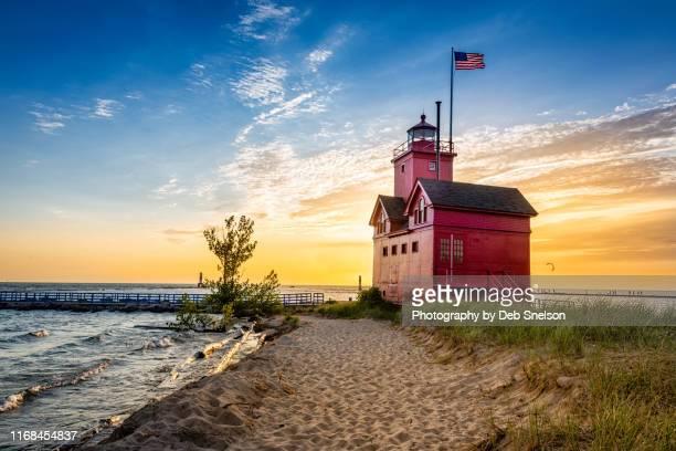 "holland harbor light ""big red"" at sunset lake michigan - lake michigan stock pictures, royalty-free photos & images"