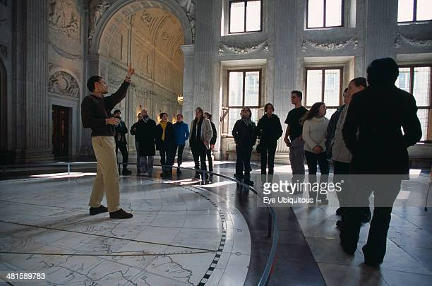Holland, Noord Holland, Amsterdam, Visitors in the Citizens Hall of the Royal Palace, with tour guide standing on a map of the Old World tiled on the...