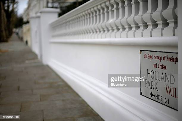 A Holland Park road sign sits on a white plastered wall outside a row of terraced houses in the Kensington and Chelsea borough of London UK on...