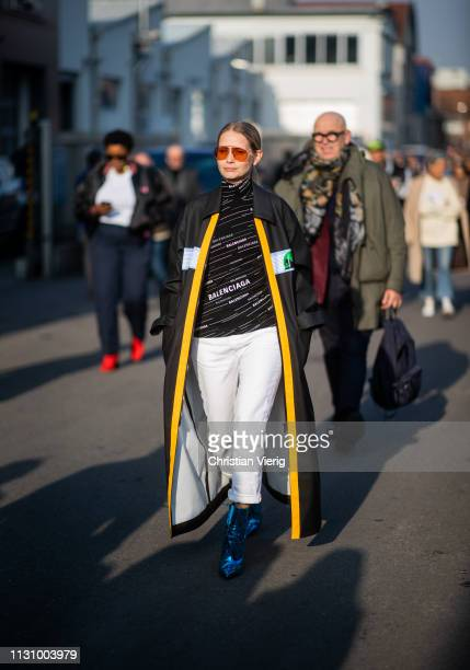 Holli Rogers is seen wearing Balenciaga top white pants black yellow coat outside Gucci on Day 1 Milan Fashion Week Autumn/Winter 2019/20 on February...
