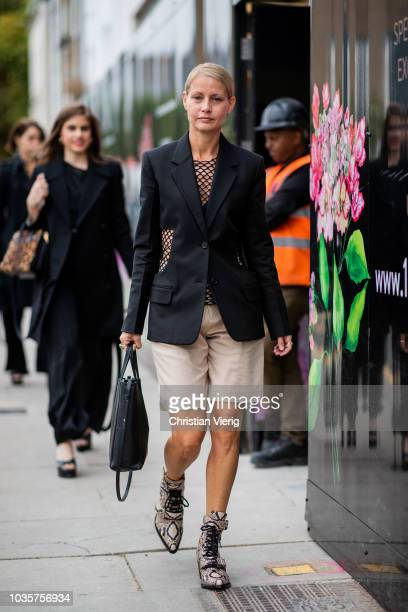 Holli Rogers wearing blazer shorts snake print boots is seen outside Natasha Zinko during London Fashion Week September 2018 on September 18 2018 in...