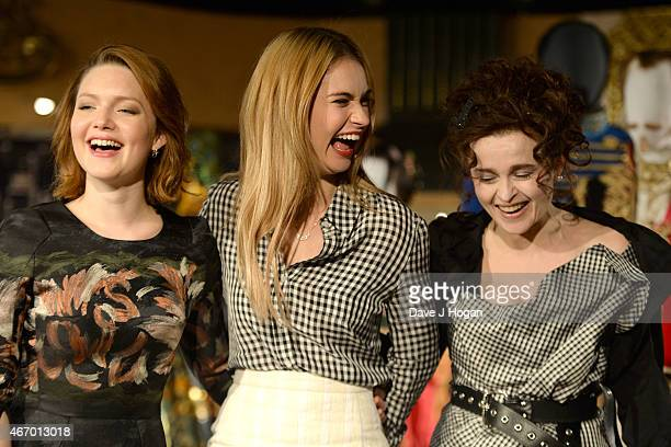 Holliday Grainger Lily James and Helena Bonham Carter pose during the Cinderella Exhibition Launch Photocall at Leicester Square on March 20 2015 in...