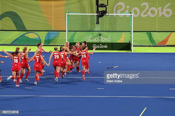 Hollie Webb of Great Britain celebrates with her team after scoring the winning penalty goal past Joyce Sombroek of Netherlands in the Women's Bronze...