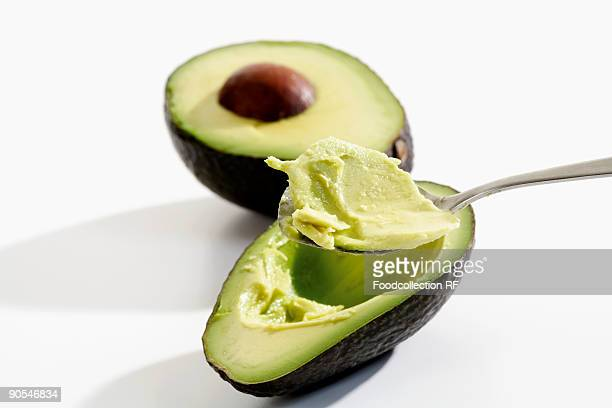 hollowing out avocado with spoon, close up - 果肉 ストックフォトと画像