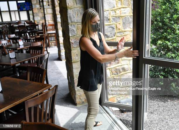 Holly Becker the Marketing Director at Stokesay Castle opens one of the floor to ceiling windows that go the length of two sides of the Knights Pub...
