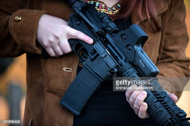 Holly Blevins holds an AR15 semiautomatic rifle December 5 2012 in Berryville Virginia Jay Blevins and his wife Holly Blevins have been preparing...