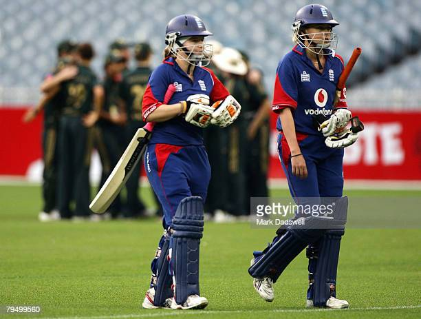 Holly Colvin and Luara Marsh of England leave the field as the Australians celebrate winning the Women's One Day International match between the...